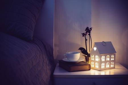 anochecer: Acogedor dormitorio por la noche entre, taza de té y una luz de noche en la mesita de noche. Inicio entre la decoración con la luz caliente. Foto de archivo