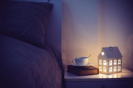 Уютный вечер интерьер спальни, чашка чая и ночной свет на прикроватном столике. Домашний интерьер декор с теплым светом.