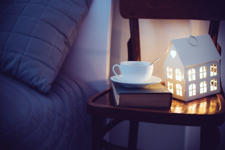 tea house: Cozy evening bedroom interior, cup of tea and a night light on the bedside table. Home interior decor with warm light.