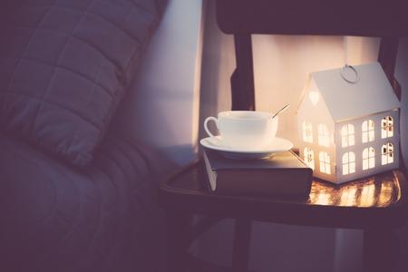 Gemütliche Abend Schlafzimmer Interieur, Tasse Tee und ein Nachtlicht auf dem Nachttisch. Startseite Interieur mit warmem Licht.