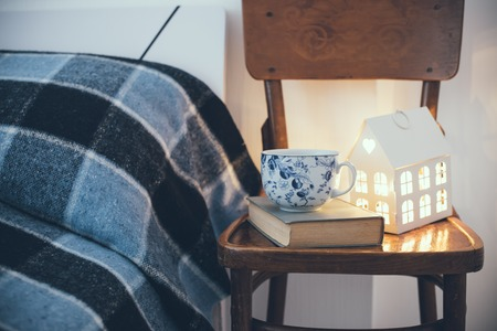 blue romance: Cozy vintage bedroom interior closeup, cup of tea and a night light on a chair. Home interior decor with blue plaid and warm light.