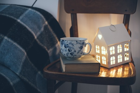 bedside: Cozy vintage bedroom interior closeup, cup of tea and a night light on a chair. Home interior decor with blue plaid and warm light.