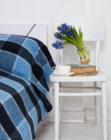 blue plaid: Clean white bedroom interior closeup, blue plaid, cup of tea and hyacinth flowers on a chair. Home interior vintage decor.
