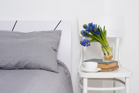 Clean white bedroom interior closeup, cup of tea and hyacinth flowers on a chair. Home interior decor.