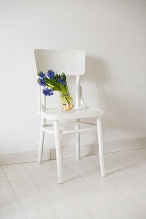 silla: flores de primavera, jacinto azul en un florero en una silla blanca de la vendimia en interior del sitio blanco.