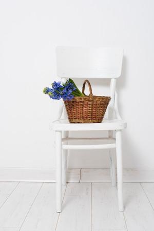 春の花と青いヒヤシンス バスケット ホワイト ルーム インテリアのヴィンテージの椅子の上でラップされたギフト。