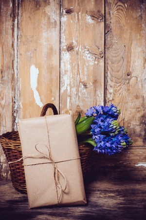 madera rústica: Spring flowers and wrapped gift, blue hyacinth on a vintage wooden board background.