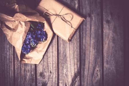 madera rústica: flores de primavera y regalo envuelto, jacinto azul sobre un fondo de tablero de madera de la vendimia.