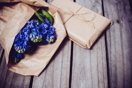 decoracion mesas: Spring flowers and wrapped gift, blue hyacinth on a vintage wooden board background.