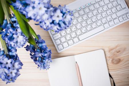紙のノートブック、コンピューターのキーボードと花を持つ作業テーブル。素敵なオフィスのクローズ アップ平面図です。 写真素材