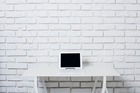 klawiatura: Minimalistic white workspace, office table with laptop near white brick wall.
