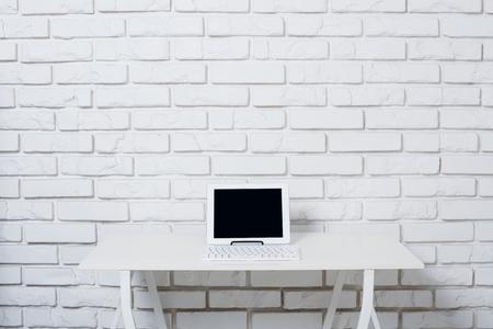 klawiatury: Minimalistyczne biały obszar roboczy, stół biurowy z laptopem w pobliżu biały mur.