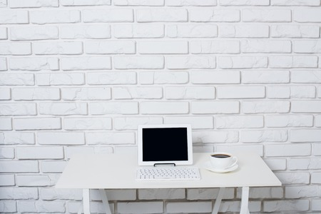 Minimalistic white workspace, office table with laptop near white brick wall.