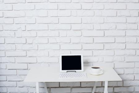 Minimalistische witte werkruimte, kantoor tafel met laptop in de buurt van witte bakstenen muur. Stockfoto