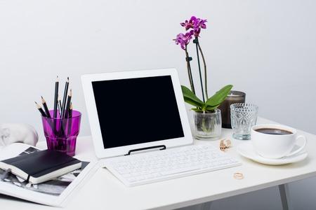 若いビジネス女性ワークスペース、白い女性オフィス インテリア クローズ アップ、蘭の花、テーブルの上のノート パソコン。