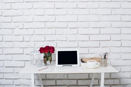 若いビジネス女性ワークスペース、白い女性オフィス インテリア クローズ アップ、バラの花、一杯のコーヒーとテーブルの上のノート パソコン。
