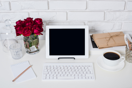 Young business woman workspace, white feminine office interior closeup, roses flowers, cup of coffee  and laptop on a table.