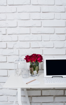 coffee table: Young business woman workspace, white feminine office interior closeup, roses flowers, cup of coffee  and laptop on a table.