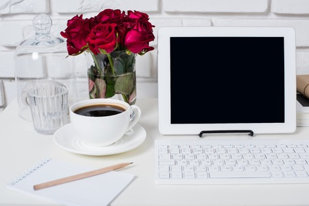 Jeune espace de travail femme d'affaires, blanc féminin gros plan intérieur de bureau, des fleurs roses, tasse de café et un ordinateur portable sur une table.