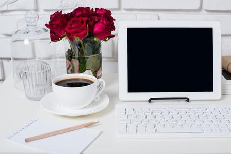 Joven mujer de negocios del área de trabajo, blanco femenino primer plano interior de la oficina, las rosas, taza de café y un ordenador portátil sobre una mesa. Foto de archivo