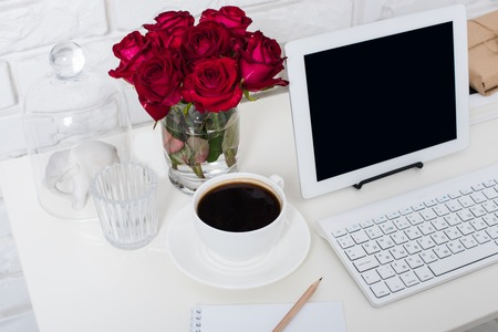 feminine: Young business woman workspace, white feminine office interior closeup, roses flowers, cup of coffee  and laptop on a table.