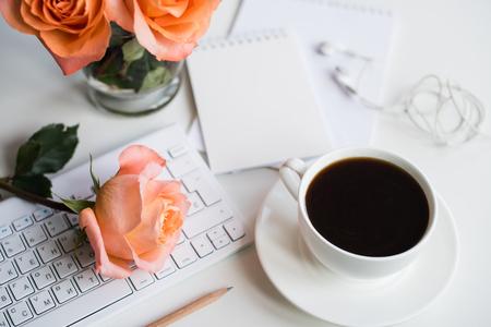Decoración de mesa de oficina blanca brillante con flores frescas, teclado de computadora y teléfono inteligente. Espacio de trabajo moderno para mujer, detalles interiores.