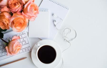 Jasny biały stół biurowy Wystrój ze świeżych kwiatów, klawiatury komputera i inteligentnego telefonu. Kobiety nowoczesne roboczy, detale wnętrza.