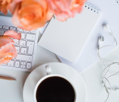 Bright white office table decor with fresh flowers, computer keyboard and smart phone. Womans modern workspace, interior details. Stock Photo
