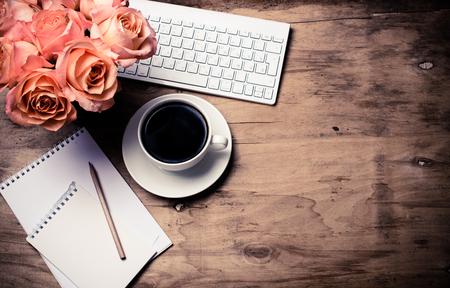 rosas naranjas: Decoración de la vendimia vector de la oficina de estilo inconformista con flores frescas, teclado del ordenador y teléfono inteligente. espacio de trabajo moderno de la mujer, detalles interiores, vista desde arriba. Foto de archivo
