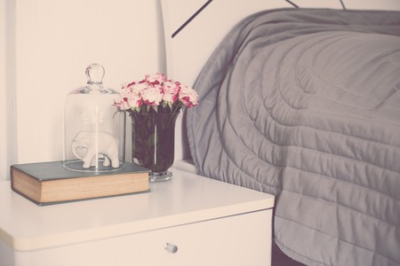 bedside: Bouquet of roses on bedside table in the bedroom, bedroom  interior close-up Stock Photo