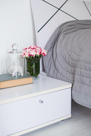 decoracion mesas: Ramo de rosas en la mesa de noche en el dormitorio, interior del dormitorio de primer plano Foto de archivo