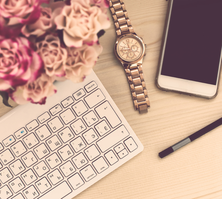 bloggers: Woman bloggers office table closeup, flowers with keyboard and smart phone on a wooden background, top view.