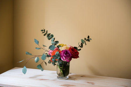 table decoration: Bouquet of colorful roses in a vase on the table, by tha wall space background. Summer home interior decor.