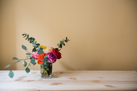 vase: Bouquet of colorful roses in a vase on the table, by tha wall space background. Summer home interior decor.