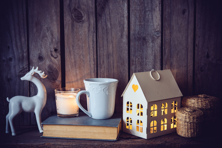 ceramic: Cozy vintage home decoration: warm interior night light, books and candles on an old wooden board background.