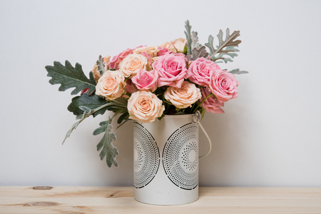 wall decoration: Bouquet of pink and beige roses in a decorative vase on a shelf in home interior, simple home decor