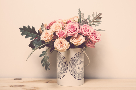 arrangements: Bouquet of pink and beige roses in a decorative vase on a shelf in home interior, simple home decor