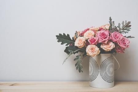 arreglo floral: Ramo de rosas de color rosa y beige en un florero decorativo en un estante en el interior casero, casera sencilla