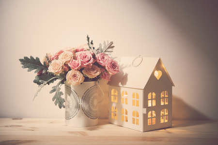 rose bouquet: Beautiful vintage home decorations: flowers and decorative objects on the shelf by the wall. House decor background. Stock Photo