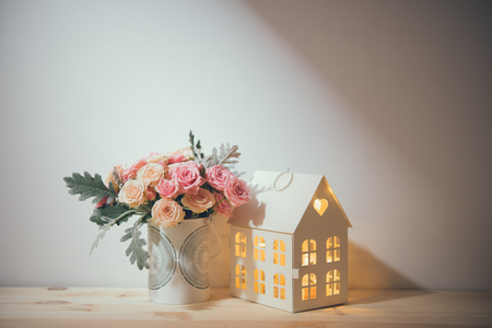 decorative objects: Beautiful vintage home decorations: flowers and decorative objects on the shelf by the wall. House decor background. Stock Photo