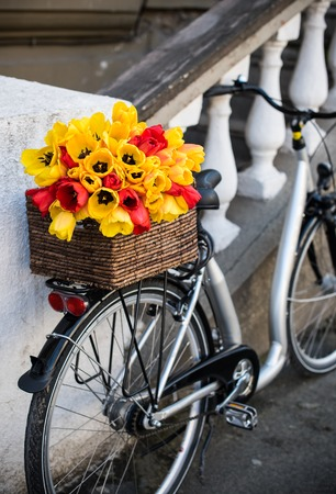 decorated bike: Beautiful city bike with a bouquet of flowers in a basket standing near the building in the street