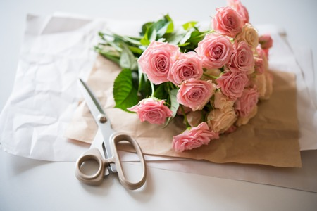 flower arrangement: Florists workspace: bouquet of fresh roses and scissors on an old vintage wooden board table.