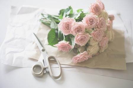 arrangements: Florists workspace: bouquet of fresh roses and scissors on an old vintage wooden board table.
