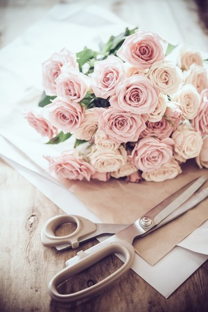 faded: Florists workspace: bouquet of fresh roses and scissors on an old vintage wooden board table.