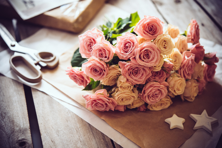 pink brown: Beautiful vintage decor: bouquet of pink roses, craft paper and decorative stars on on old wooden table. Stock Photo
