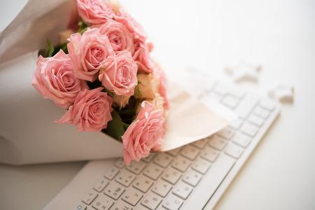 흰색 컴퓨터 키보드에 핑크와 베이지 색 장미 꽃다발, 현대 직장 근접 촬영