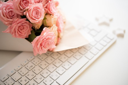 bouquet fleur: Bouquet of pink and beige roses on white computer keyboard, modern workplace closeup