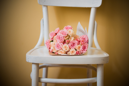 rosas blancas: Ramo de rosas de color rosa y beige en una vieja silla de la vendimia.