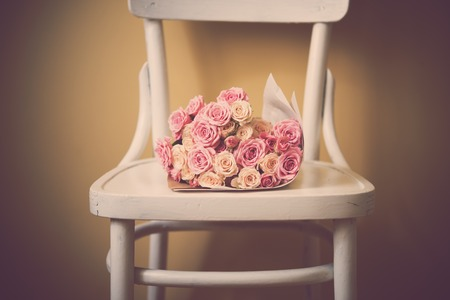 pink brown: Bouquet of pink and beige roses on an old vintage chair.