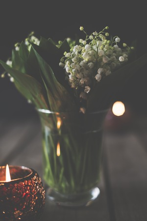 simple life: Simple home decoration, lilies of the valley in a vase on a rustic table, dark moody still life